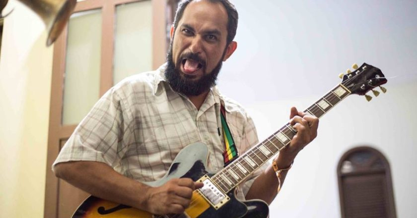 Músico Zé Caxangá tocando guitarra